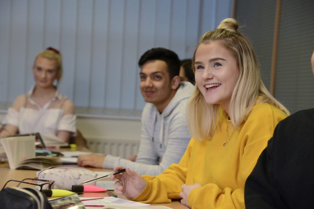 Girl smiling wearing a yellow jumper and her bob hairstyle half tied up, sitting next to her peer wearing a white jumper and looking eagerly toward someone who is speaking but you cannot see