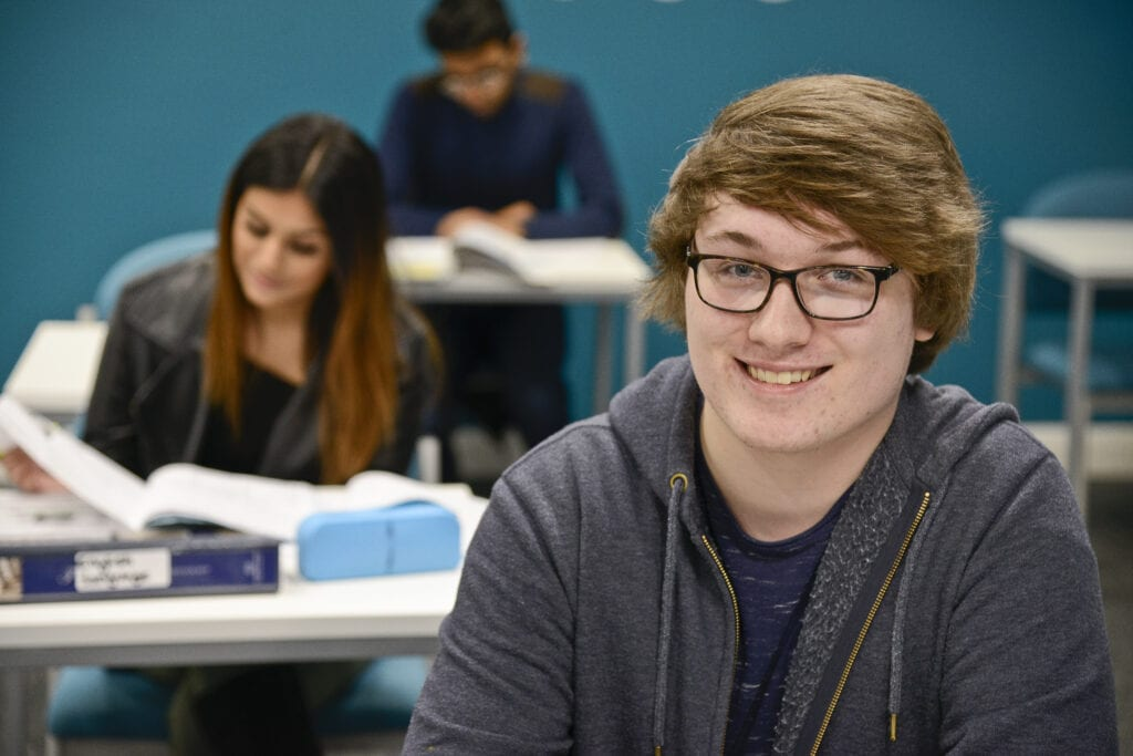 Young man smiling at the camera sat at within the silent study zone