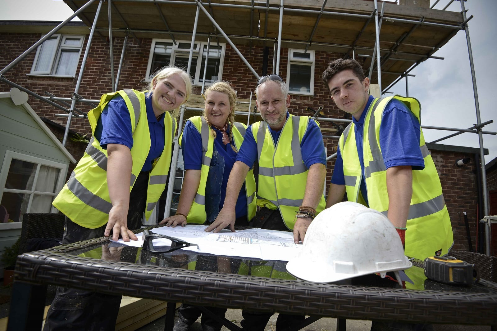 Two employers with their two apprentices, in front of a house with scaffolding with them gathered round looking at plans for the site